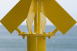Yellow no sail metallic buoy on blue sea background
