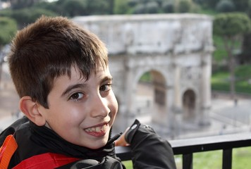 Smiling boy in front of Arch of Constantine in Rome