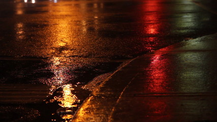 Rainy night. Traffic lights green, amber, red.