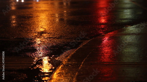 Rainy night. Traffic lights green, amber, red.