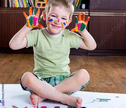 Cute happy boy painting