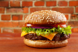 Hamburger on table with red brick wall background