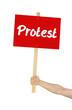 Person hält Schild mit der Aufschrift Protest
