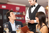 Waiter serving a couple at restaurant