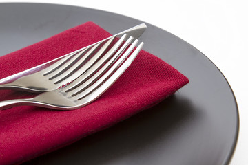 Cutlery on red napkin with plate