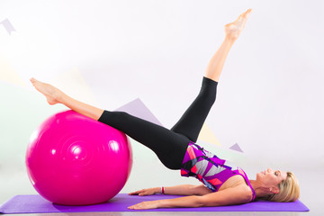 beautiful pilates instructor with pink ball and purple yoga mat