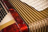 Red accordion and sheet music, closeup