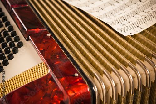 Leinwanddruck Bild Red accordion and sheet music, closeup