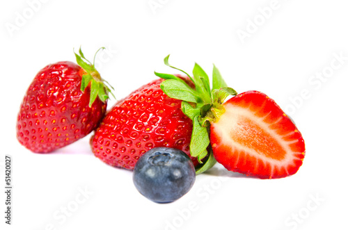 Isolated strawberries with a bilberry on white