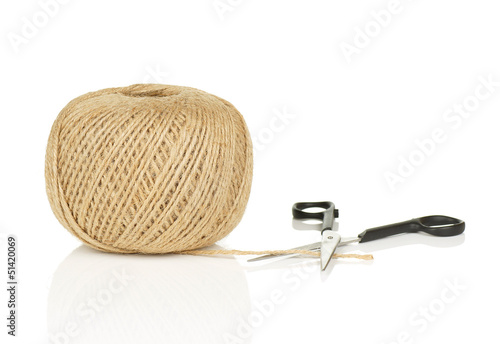 Ball of String with Scissors Cutting End on White