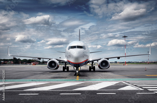 canvas print picture Total View Airplane on Airfield with dramatic Sky