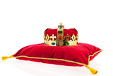 Golden crown on velvet pillow