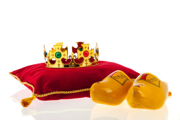 Golden crown on velvet pillow with Dutch wooden clogs