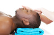 Black man recaiving head massage at spa.