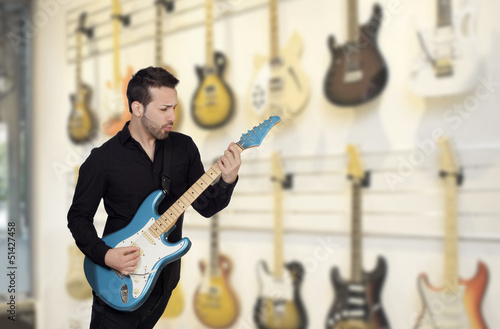 Attractive men playing a electric guitar