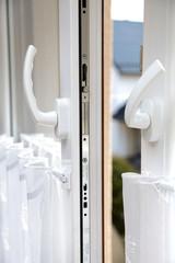 Okno współczesne białe z klamkami i mechanizmem do otwierania.
