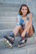 smiling roller girl sitting on the stairs