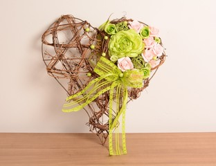 Decorative wicker heart with purple and green rose.