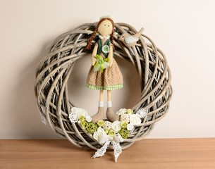 Interior decoration, wicker wreath with rose and doll.