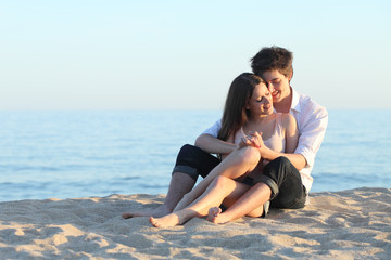 Couple embracing sitting on the sand of the beach