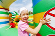 Joyful little girl has fun at inflatable attractions in park