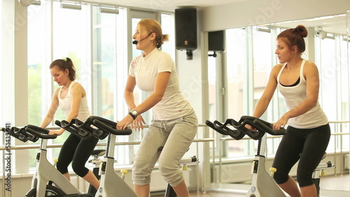 Group of women working out on bicycles  in the gym