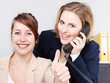 Two business women work in the office, show thumb up