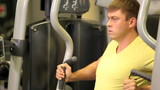 Athletic man exercising on sport machine in fitness center