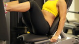 Beautiful woman training on sport machine in gym