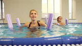 Group of women with aqua tubes doing exercise in swimming pool