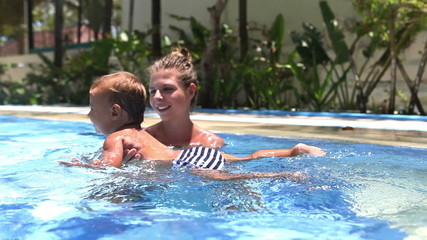Happy mother teaching to swim daughter in swimming pool