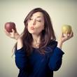 beautiful woman choosing red or yellow apples