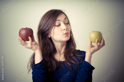 beautiful woman choosing red or yellow apples