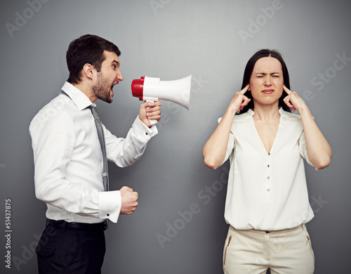 man screaming in megaphone at the woman