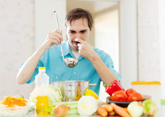Man with ladle testing foul food