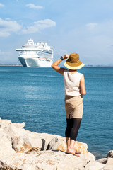 Woman with hat stands and looks at the sea, a cruise ship