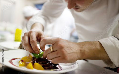 Aluminium Vlees Chef in restaurant kitchen cooking, only hands to be se