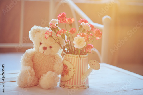 Still life with teddy bear and pink flowers in the watering can