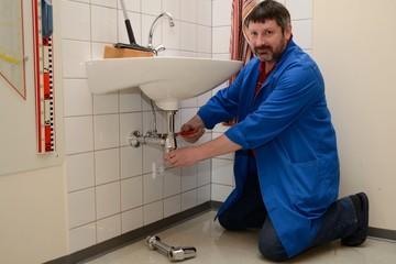 Hausmeister repariert Waschbecken
