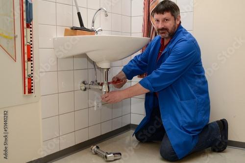 Leinwanddruck Bild Hausmeister repariert Waschbecken