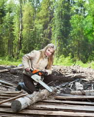 The young woman in wood saws a tree a chain saw..
