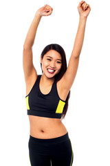 Joyous female raising arms in excitement