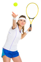 Female tennis player serving ball