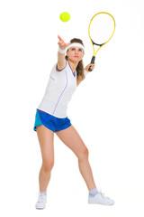 Full length portrait of female tennis player serving ball