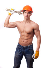 Muscular young worker a wrench on a white background.