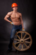 Muscular young man with a wagon wheel on a black background.