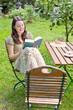 junge Frau bließt ein Buch im Garten