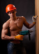 Muscular young worker with an electric drill