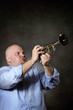 Man with strong and focused expression plays a trumpet