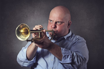 Man with strong expression plays a trumpet
